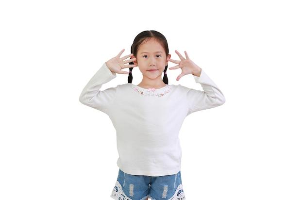 Porträt des friedlichen asiatischen kleinen kindermädchens, das zehn finger lokalisiert auf weiß zeigt Premium Fotos