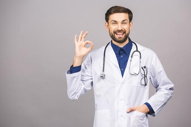 Porträt des fröhlich lächelnden jungen arztes mit stethoskop über hals im medizinischen mantel ok zeichen.