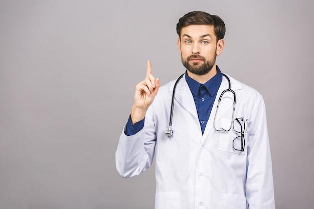 Porträt des fröhlich lächelnden jungen arztes mit stethoskop über hals im medizinischen mantel