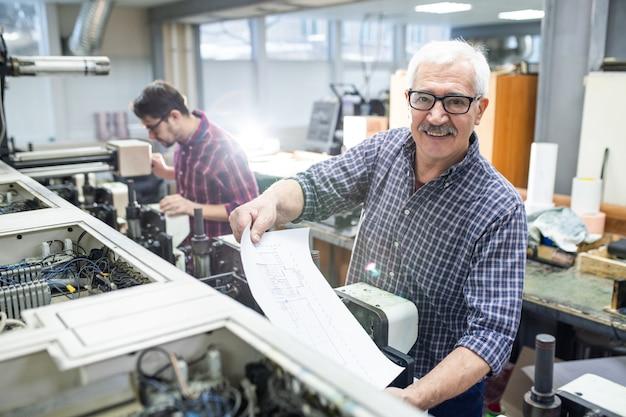 Porträt des fröhlichen älteren mannes in den gläsern, die gedrucktes papier aus druckmaschine in der fabrik erhalten