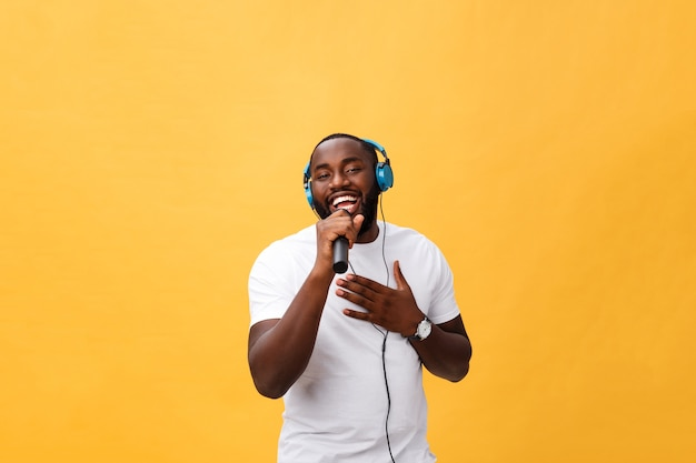 Porträt des fröhlichen afrikanischen mannes, der mikrofon hält und kopfhörer auf kopf hat, der musik singendes lied hört