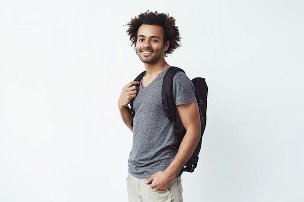 Porträt des fröhlichen afrikanischen mannes mit dem lächelnden rucksack, der bereit ist, auf eine lange wanderreise zu gehen oder nach bildung zu streben