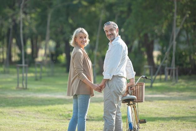 Porträt des fröhlichen aktiven älteren paares mit dem fahrrad, das zusammen durch park geht. perfekte aktivitäten für ältere menschen im ruhestand.