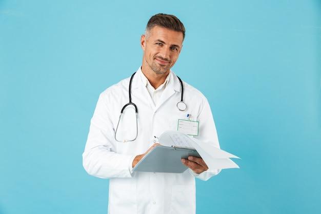 Porträt des fröhlichen arztes mit stethoskop, das gesundheitskarte hält, lokalisiert über blauer wand