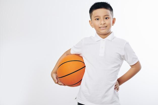 Porträt des fröhlichen asiatischen jugendlichen jungen, der mit basketballball aufwirft und kamera betrachtet
