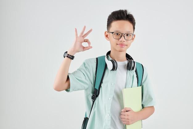 Porträt des fröhlichen asiatischen schuljungen mit heft, das ok zeichen zeigt und schaut