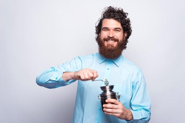 Porträt des fröhlichen bärtigen mannes im lässigen halten der manuellen kaffeemühle und des lächelns.