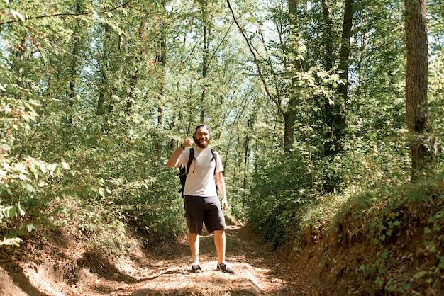 Porträt des fröhlichen bärtigen wandermannes mit rucksack, der daumen oben zeigt.