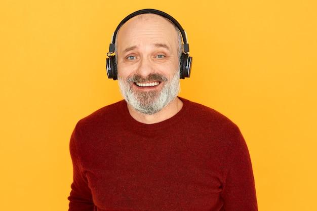 Porträt des fröhlichen emotionalen älteren mannes mit dem dicken grauen bart, der unter verwendung der drahtlosen kopfhörer lokalisiert aufwirft
