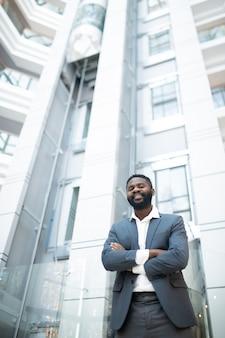 Porträt des fröhlichen erfolgreichen jungen afroamerikanischen geschäftsmannes im anzug, der mit verschränkten armen in der bürolobby steht