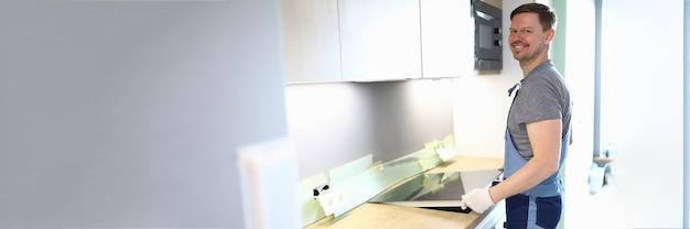 Porträt des fröhlichen handwerkers, der kochherd auf küche setzt. professioneller servicemitarbeiter in uniform, der beim umzug hilft. neue eigenschaft. renovierungs- und innenarchitekturkonzept