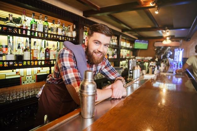 Porträt des fröhlichen jungen barkeepers, der in der bar steht und lächelt