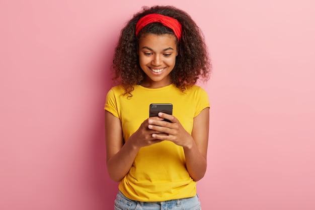Porträt des fröhlichen jungen mädchens mit dem lockigen haar, das im gelben t-shirt aufwirft