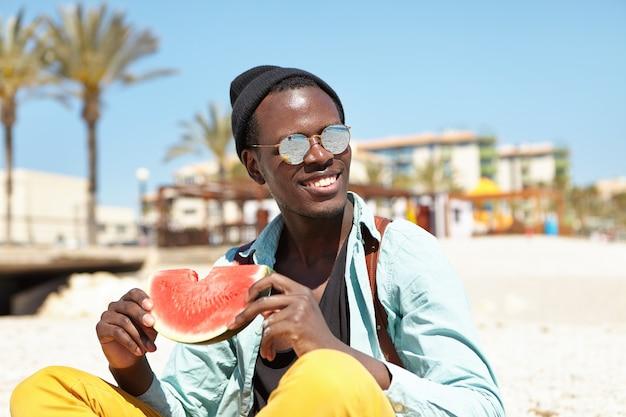 Porträt des fröhlichen jungen mannes, der sich am städtischen strand entspannt, der scheibe der reifen wassermelone hält