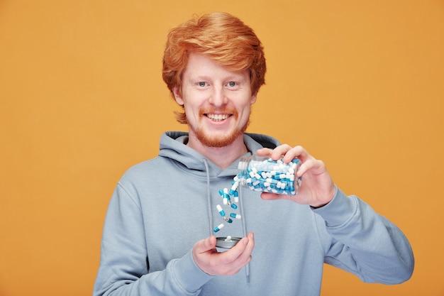 Porträt des fröhlichen jungen rothaarigen mannes mit käsigem grinsen, das pillen von flasche auf orange entleert