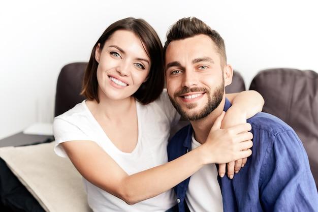 Porträt des fröhlichen jungen schönen paares, das auf sofa sitzt und lächelt, mädchen, das freund umarmt