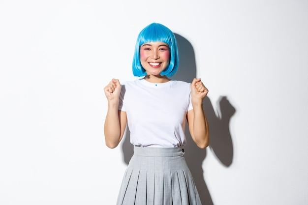 Porträt des fröhlichen kawaii asiatischen mädchens in der blauen parteiperücke, die den sieg feiert, glücklich lächelt und von der freude springt, über erfolg triumphiert, stehend.