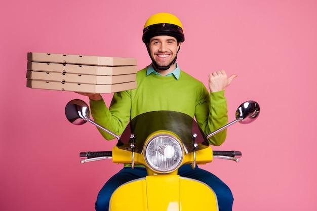 Porträt des fröhlichen kerls, der motorrad fährt, das pizza direkt fingerseite trägt