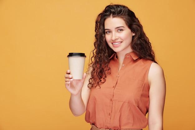 Porträt des fröhlichen lockigen mädchens im ärmellosen hemd, das kaffee trinkt, um auf orange zu gehen