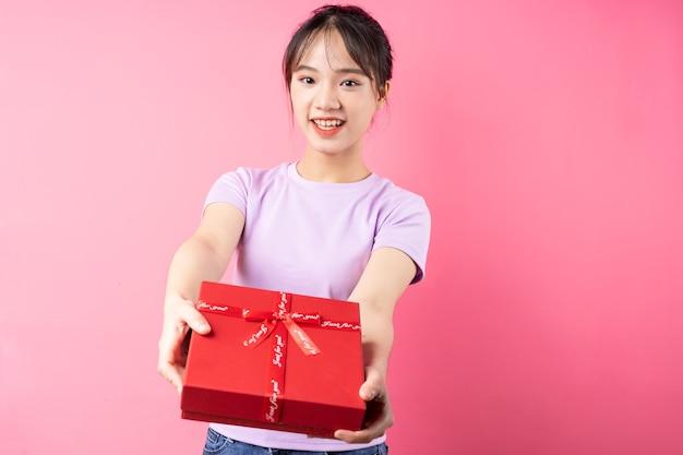 Porträt des fröhlichen mädchens, das geschenkbox in der hand hält, lokalisiert auf rosa hintergrund