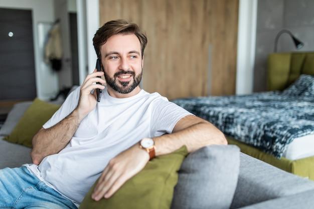 Porträt des fröhlichen mannes, der am telefon spricht, das an der couch zu hause sitzt