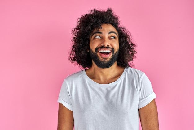 Porträt des fröhlichen positiven mannes des arabischen aussehens, das lachend wegschaut