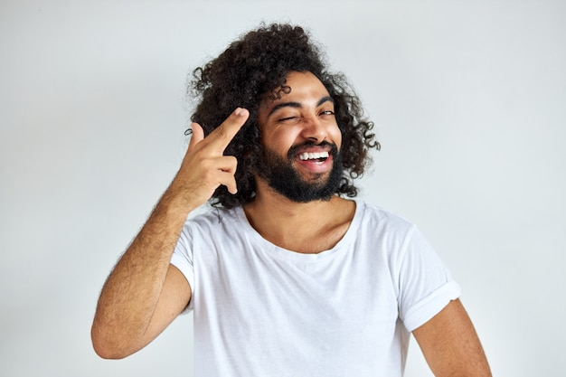 Porträt des fröhlichen positiven mannes des arabischen aussehens, der lachend wegschaut, hört er witz