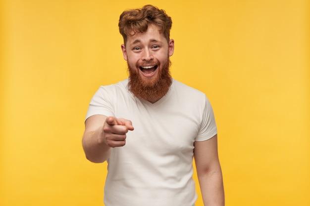 Porträt des fröhlichen positiven mannes mit rotem bart trägt leeres t-shirt, lacht und zeigt mit einem finger nach vorne