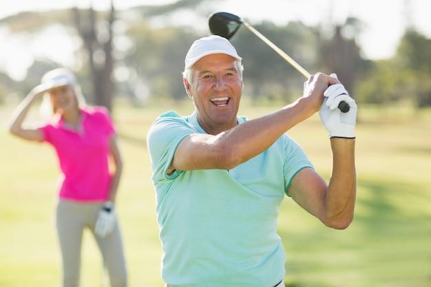 Porträt des fröhlichen reifen golfers, der golfschläger hält
