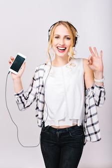 Porträt des fröhlichen schönen blonden mädchens, das musik hört, lächelt und schaut. freizeitzeit der hübschen jungen frau, die trendige weiße bluse und schwarze hose trägt.