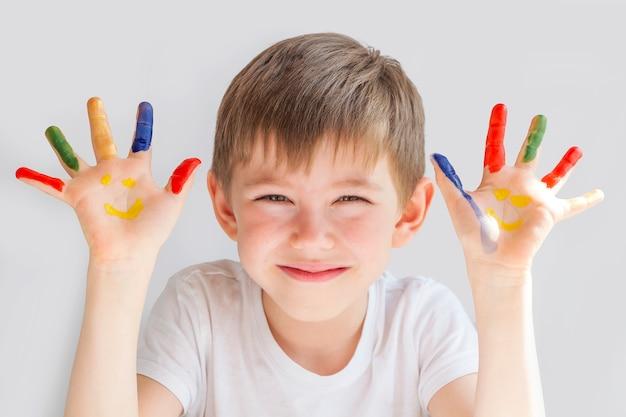 Porträt des fröhlichen süßen kleinen jungen im vorschulalter 5-6 jahre mit bunt bemalten händen. smiley-hände. fingerzeichnung, bildung und kinderentwicklung. glückliche kindheit.