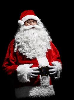Porträt des fröhlichen weihnachtsmannes mit den händen auf dem bauch