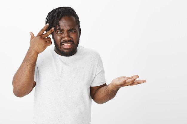 Porträt des frustrierten kerls mit zöpfen, die gegen die weiße wand aufwerfen