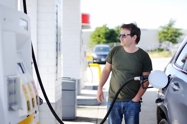 Porträt des füllenden benzinkraftstoffs des mittelaltermannes im auto