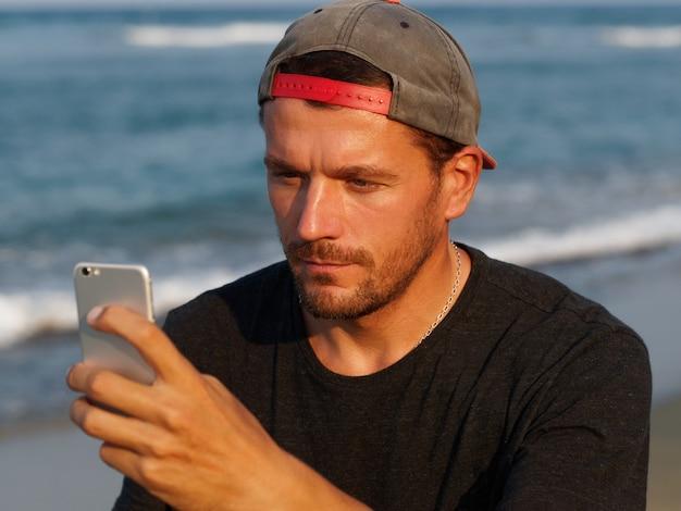 Porträt des gebräunten mannes am strand mit handy. lebensstile.