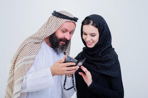 Porträt des gekleideten paares der arabischen weise spielen mit handy.