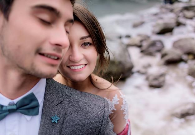 Porträt des gelächelten kaukasischen paares, des brünetten jungen und des mädchens gekleidet in der offiziellen kleidung im freien