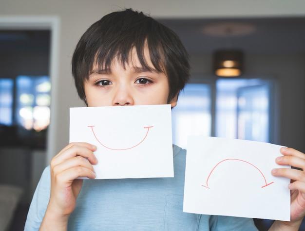 Porträt des gelangweilten kindes mit dem traurigen gesicht, das weißes papier mit lächeln und traurig hält, kinderjunge, der geboren wird, bleibt während der selbstisolierung, quarantäne zu hause. coronavirus-ausbruch und grippe-covid-epidemie