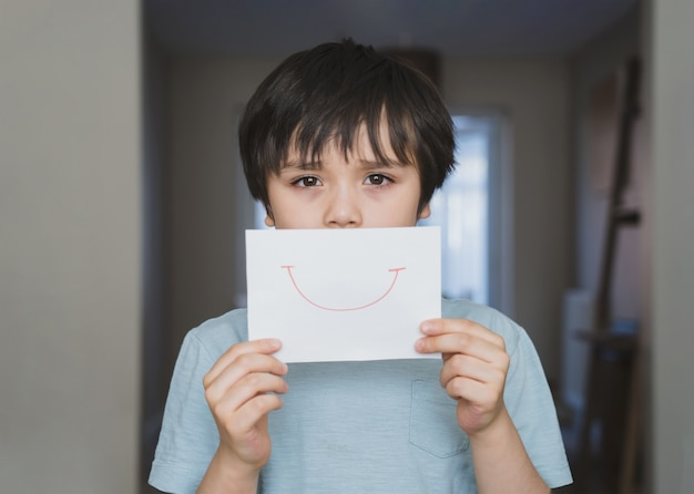 Porträt des gelangweilten kindes mit traurigem gesicht, das weißes papier mit lächeln hält, kinderjunge, der geboren wird, bleibt während der selbstisolation zu hause