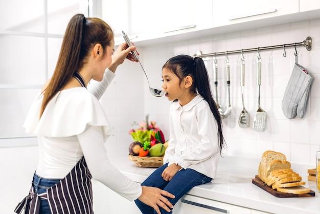 Porträt des genießens der glücklichen liebe asiatische familienmutter und des kleinen asiatischen mädchenkindes lächelnd und vorbereitung des kochens des frühstücks zusammen in der küche zu hause