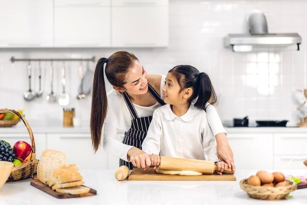 Porträt des genusses der glücklichen liebe der asiatischen familienmutter und des kleinen asiatischen mädchen-tochterkindes, die spaß beim kochen zusammen mit dem backen von keksen und kuchenbestandteilen auf dem tisch in der küche haben