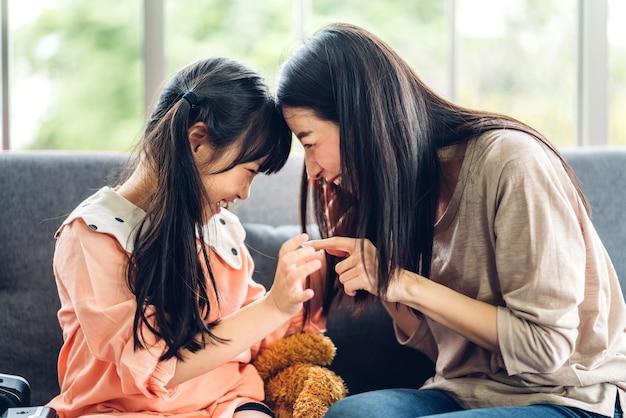 Porträt des genusses der glücklichen liebe der asiatischen familienmutter und des kleinen asiatischen mädchenkindes, das lächelt und spaß hat
