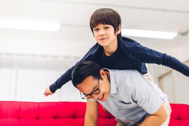Porträt des genusses der glücklichen liebe des asiatischen familienvaters, der kleinen asiatischen jungensohn auf dem rücken trägt, der lächelnd superhelden spielt und lustige momente gute zeit zu hause hat