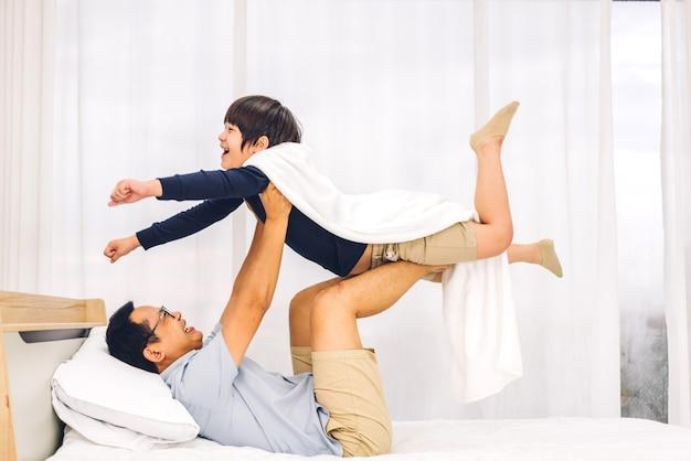 Porträt des genusses der glücklichen liebe des asiatischen familienvaters, der kleinen asiatischen jungensohn trägt, der lächelnd superhelden spielt und lustige momente gute zeit auf dem bett zu hause hat
