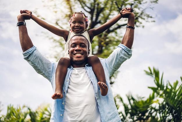 Porträt des genusses der glücklichen liebe schwarzer familie afroamerikaner-vater, der tochter kleines afrikanisches mädchenkind trägt, das lächelt und spaßmomente gute zeit im sommerpark zu hause hat