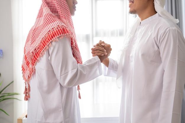 Porträt des geschäftlichen muslimischen partners händeschütteln in der besprechung