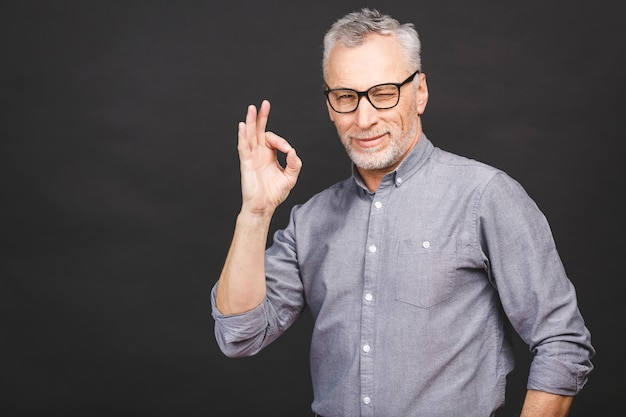 Porträt des geschäftsmäßigen älteren mannes der 50er jahre mit grauem haar und bart im hemd lächelnd und gestikulierendes ok zeichen lokalisiert gegen schwarze wand.