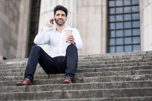 Porträt des geschäftsmannes, der am telefon spricht, während auf treppen draußen sitzt