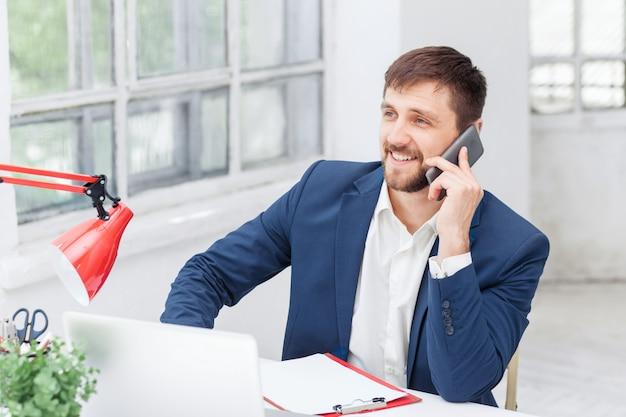 Porträt des geschäftsmannes, der auf handy im büro spricht
