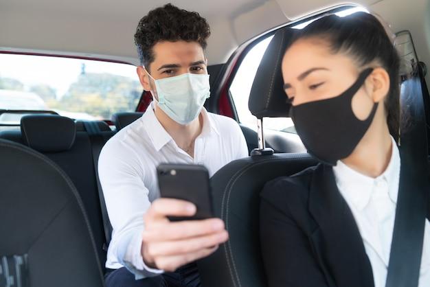 Porträt des geschäftsmannes, der dem taxifahrer etwas auf seinem telefon zeigt. unternehmenskonzept